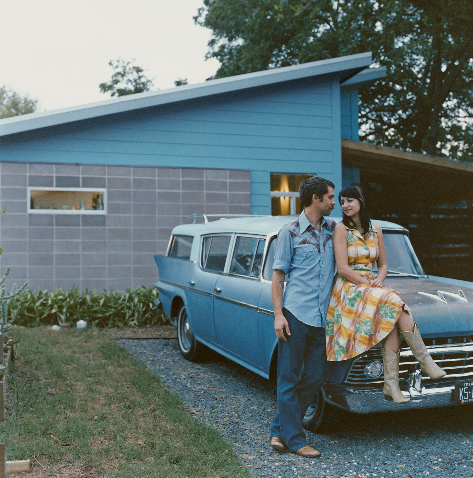 Exterior and House Building Type Andy and Regina Rihn lean on their other blue-clad affordable design, a 1958 AMC Rambler Super station wagon, in front of their house in Austin, Texas.  Photos from A Lot for a Little