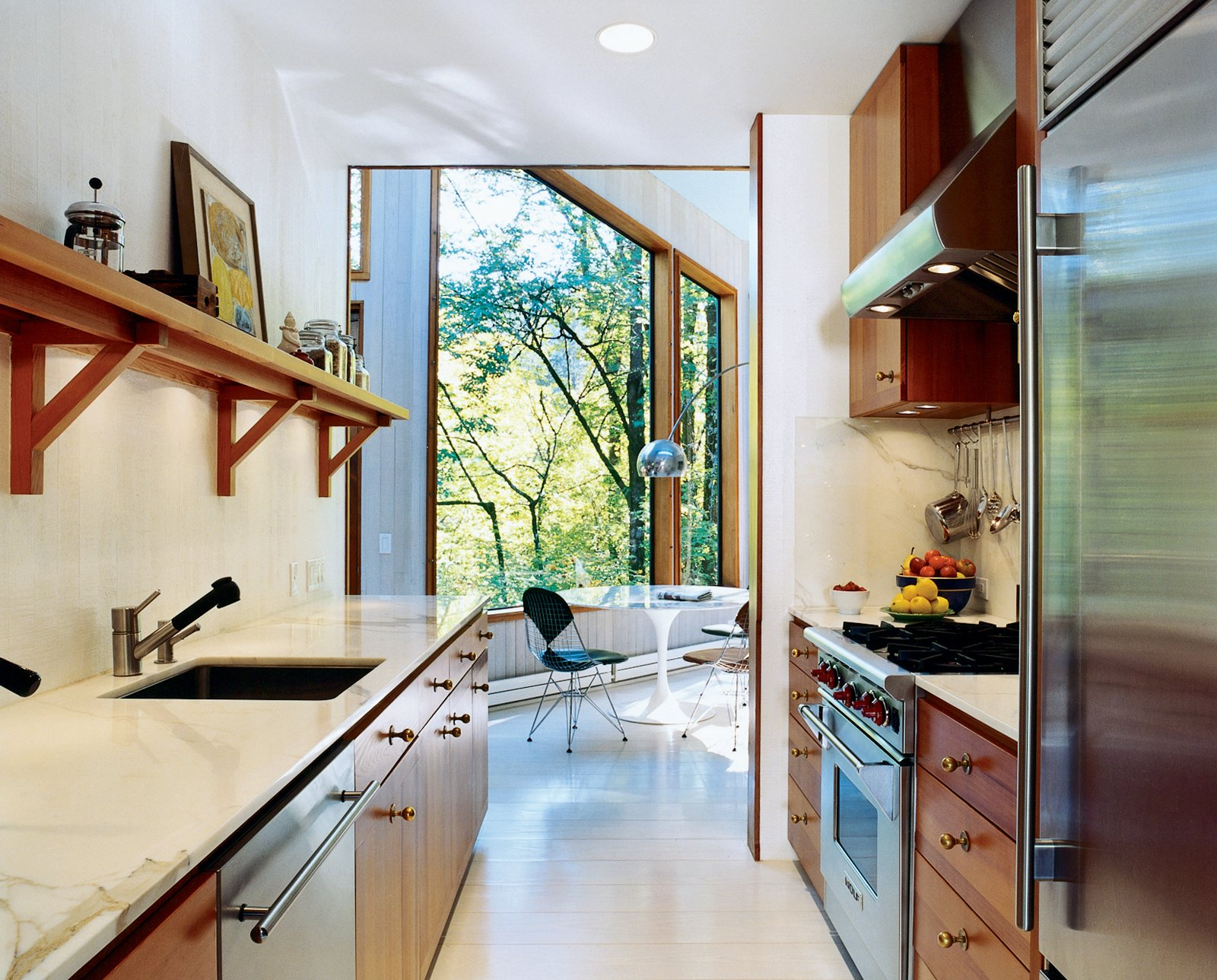 Kitchen, Marble Counter, Refrigerator, Range, and Marble Backsplashe To brighten the kitchen, which was once the darkest room, Watson and Tschopp decided on a glossy white finish, painted directly on the same rough-cut cedar paneling used throughout the house. This maintains the consistency of materials and texture, while reflecting light and enhancing the natural illumination. Stainless steel appliances and vintage bronze hardware add luster. Super White semigloss (walls) and Old Pick Up Blue (ceilings) are by Benjamin Moore.  Photo 3 of 6 in The Pace of Portland