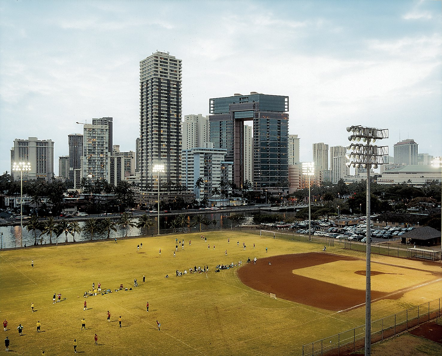 In the shadow of Waikiki's high-rises, a twilight soccer game unfolds at the Ala Wai Neighborhood Park. The now-polluted Ala Wai Canal was created in the 1920s to drain the swampland that would become Waikiki.  Photo 1 of 16 in Honolulu, Hawaii