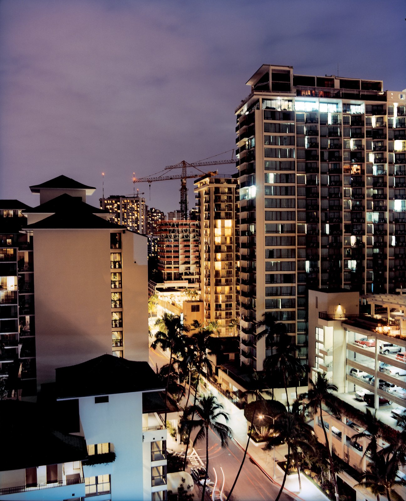 A crane-dotted night sky over Waikiki's condos and hotels attests to the city's recent building boom, as developers rush to accommodate the area's teeming 4.5 million visitors per year.  Photo 5 of 16 in Honolulu, Hawaii