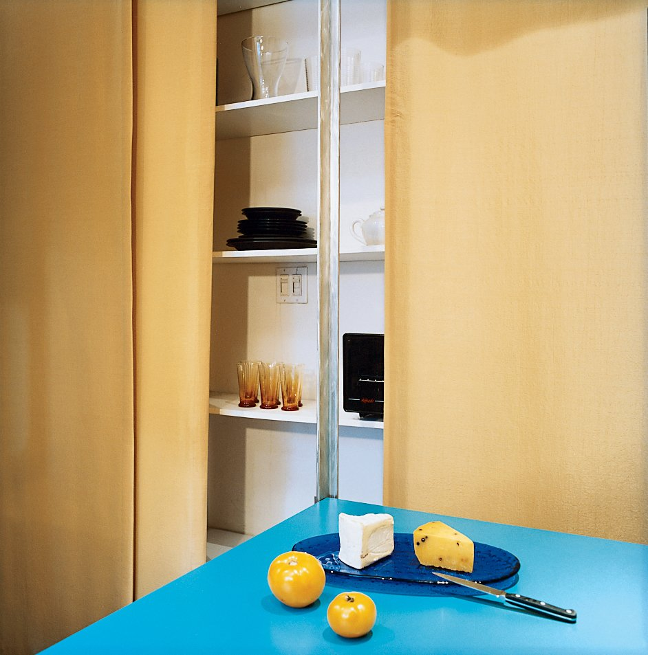 Hughston keeps all his tableware behind the curtain, on the shelves nearest the kitchen. The ample shelf space, covering the entire wall (except that taken up by the Murphy bed), makes it easy for Hughston to avoid mess. The contrast of gold and turquoise is warm and lively.  Photo 3 of 6 in A 400-sq-ft New York Apartment Gets a Second Chance