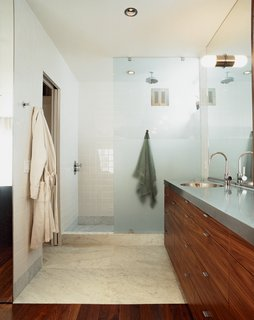 The unifying elements of walnut and steel—with a little marble and concrete thrown in—continue downstairs in the bathroom and bedroom.