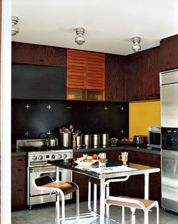 """Charles de Lisle, of the interior design firm Your Space, designed the kitchen backsplash of PVC rubber flooring embedded with stainless steel """"plus"""" signs. The restaurant supply table is flanked by steel-and-wood Lem Piston stools from Design Within Reach."""