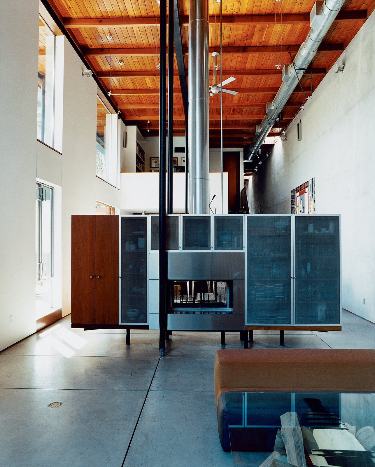 David Baker and cabinetmaker Thomas Jameson designed the freestanding fireplace / media console, which effectively divides the more formal living room from the dining and gathering space while concealing cords and other clutter.  97+ Modern Fireplace Ideas from The New Suburbanism