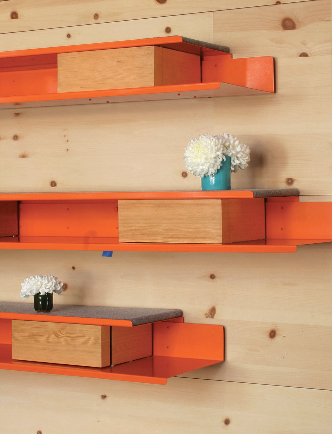 Robertson designed the orange powder-coated-steel shelves and storage units that line the knotty-pine walls.  Courtyard House by David A. Greene