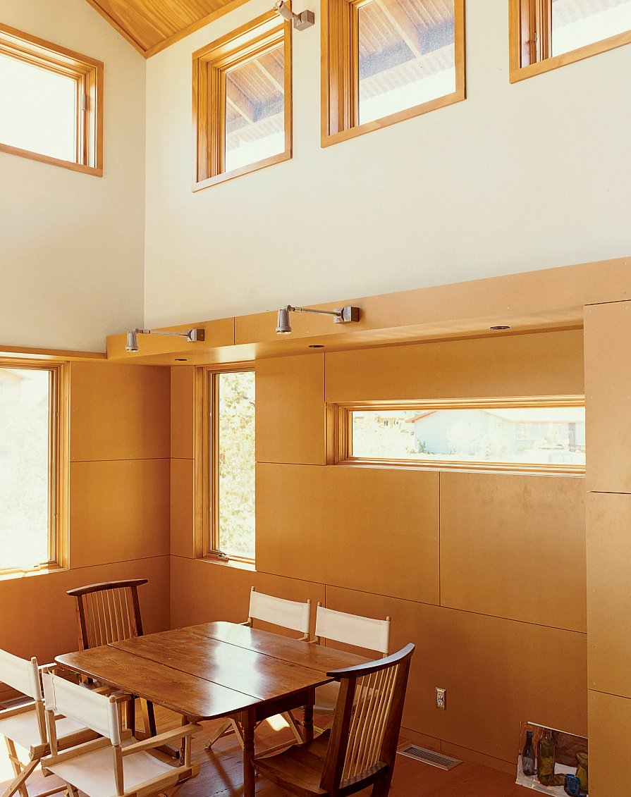 Dining Room, Chair, Table, Wall Lighting, and Medium Hardwood Floor Light pours into the Ankneys' living/dining area with its clear pine plywood ceiling, clear-finish MDF paneling on the walls, and reclaimed-fir flooring.  Photo 4 of 10 in Jackson, WY