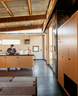 Architect Eric Logan sits in the guest house. The interiors are made up of oiled masonite wall paneling, raw MDF cabinetry, and an oiled concrete floor.
