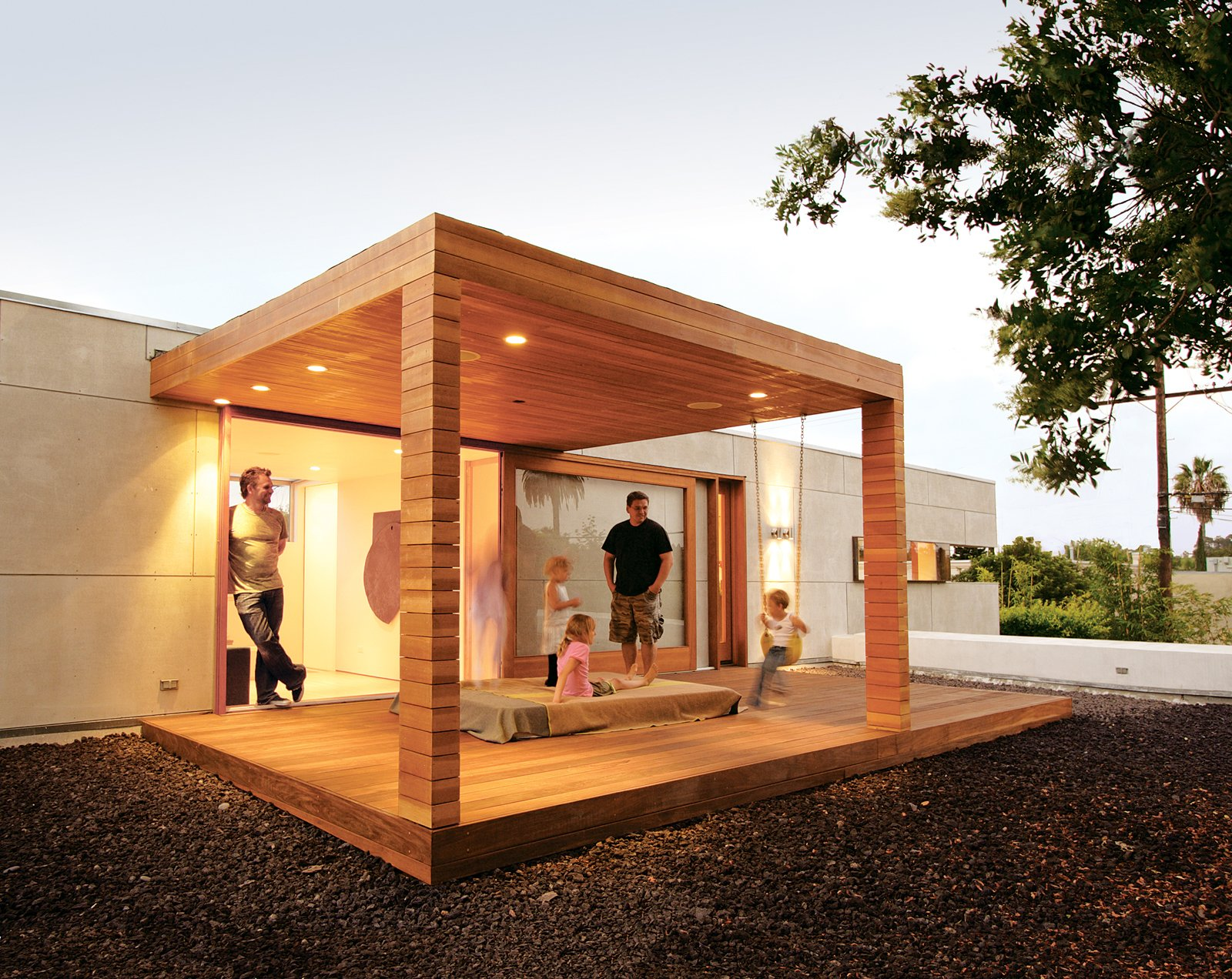 Outdoor, Small Patio, Porch, Deck, Wood Patio, Porch, Deck, Back Yard, Hardscapes, and Trees Thorsteinsson (above left, standing in doorway) relaxes with his daughter Carmen   Inga (standing) and friends on the outdoor sleeping pavilion. The platform is surrounded by   black lava rock, which acts as a deterrent to keep children away from the edge of the second-story deck.  Photo 2 of 5 in Building Green in Santa Monica