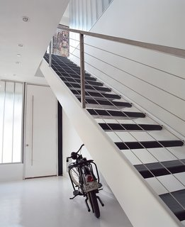 The home's entryway features fly-ash concrete floors and stairs cut from recycled steel.