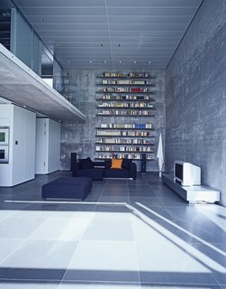 The cavernous living room takes advantage of its height with floor-to-ceiling bookshelves.