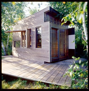 The exterior is clad in an elegant mish-mash of cedar, plywood, glass, and fiberglass panels.