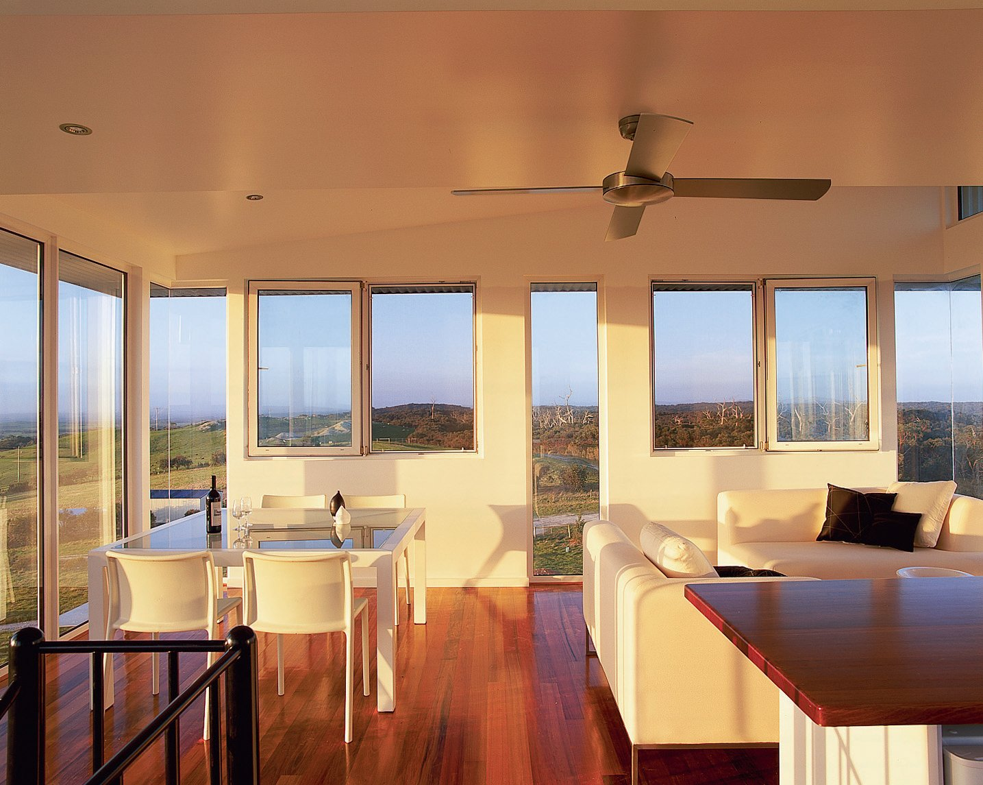 Living Room, Sectional, and Medium Hardwood Floor Walls of windows in the kitchen and living area frame uninterrupted views of a forest and the ocean.  Photo 3 of 3 in Rising to the Occasion