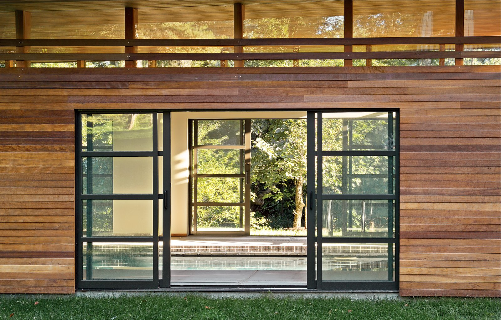 Doors Sliding glass doors open to reveal the interior of the pool house, which boasts a line of clerestory windows just below the roof.  Shining Examples of Clerestory Windows by Luke Hopping from Skinny Dip