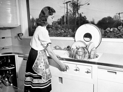 Mrs. Fritz Burns in her dream kitchen, using her built-in hydraulic dishwasher, in a Los Angeles house designed and built in 1946 in by her contractor husband, Bob Landry.  Kitchen from Yesterday's Kitchen of Tomorrow