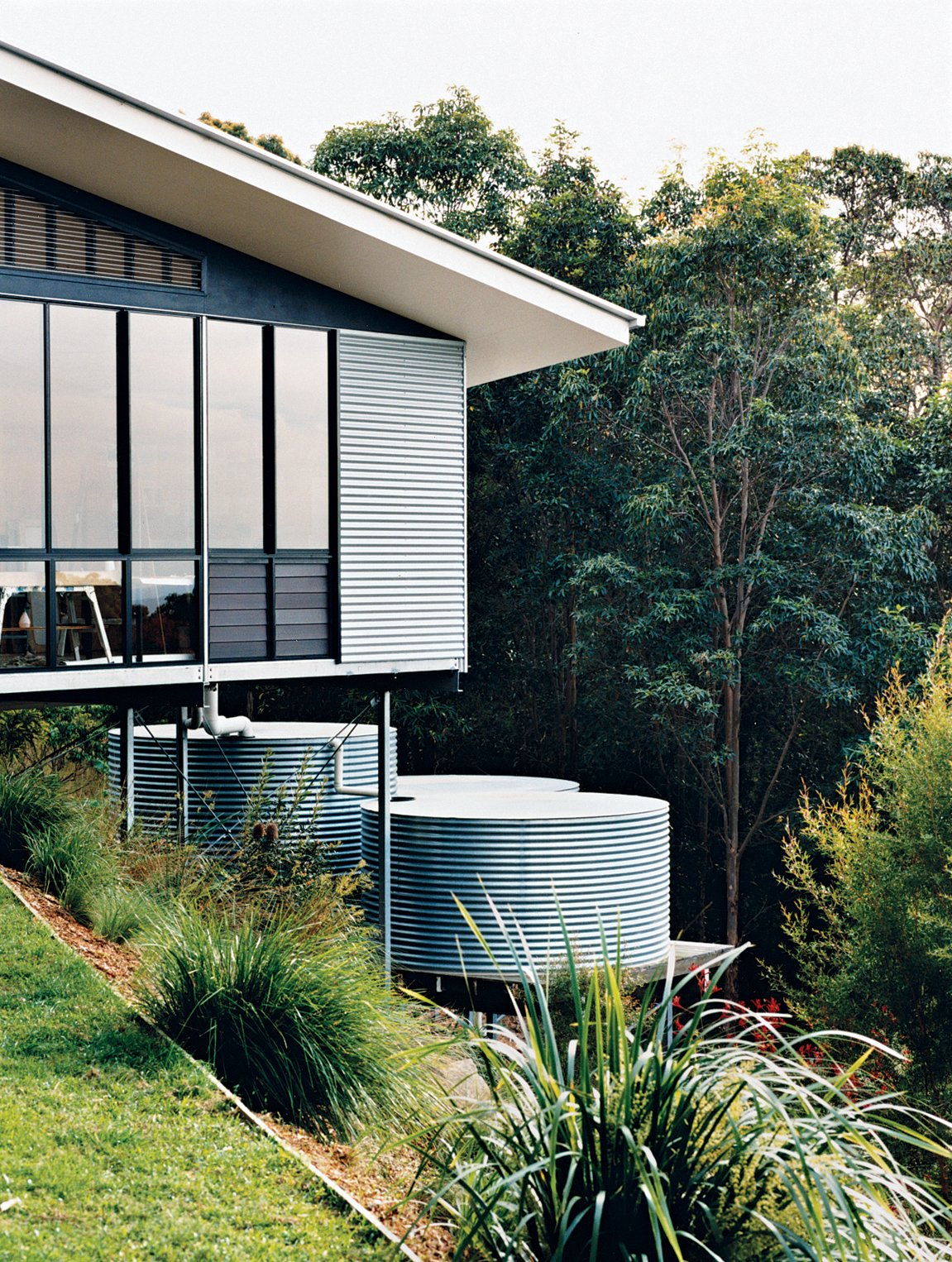 Outdoor and Grass The studio is clad in corrugated tin, echoing the adjacent water-storage tanks, which collect and filter rainwater off the roof.  Photo 7 of 12 in Hillside Family Home in Australia