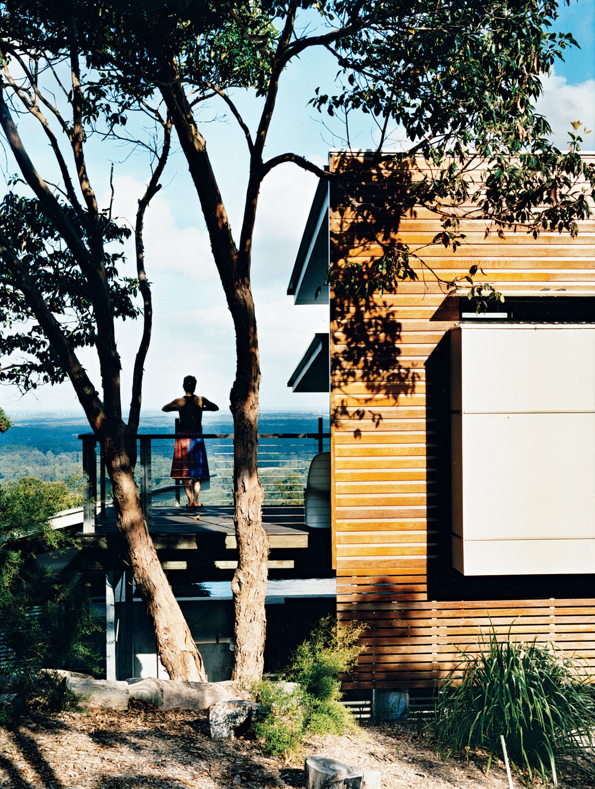"""Exterior and Wood Siding Material Webb surveys the view from the """"lookout deck"""" off the bedroom.  Photo 10 of 12 in Hillside Family Home in Australia"""