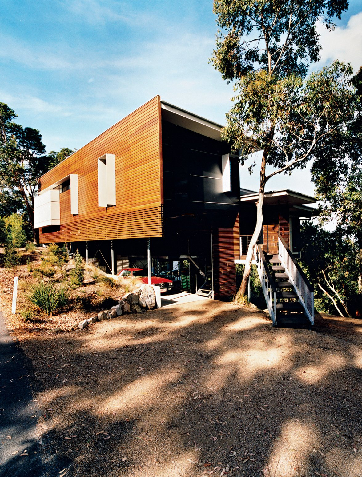 Exterior, House Building Type, and Wood Siding Material Batten screens of spotted gum wood sheath the house and allow ventilation into the outdoor storage area.  Photo 11 of 12 in Hillside Family Home in Australia