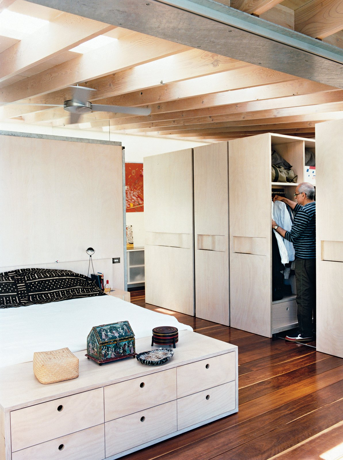 Bedroom, Bed, Storage, Night Stands, Table Lighting, Dark Hardwood Floor, and Wardrobe The bedroom contains an ingenious closet system similar to library stacks. These large sliding cabinets open up to make way for Zulaikha and Laurence as they hang their clothes or access anything else kept in storage.  Surprising Clothing Storage Solutions by Jaime Gillin from A Measured Approach