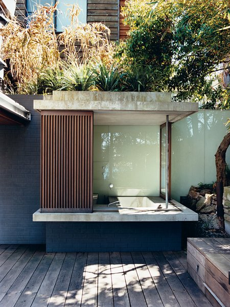 The glass and wood walls of the bathhouse, like other retractable panels on the house,   offer shade with a view.