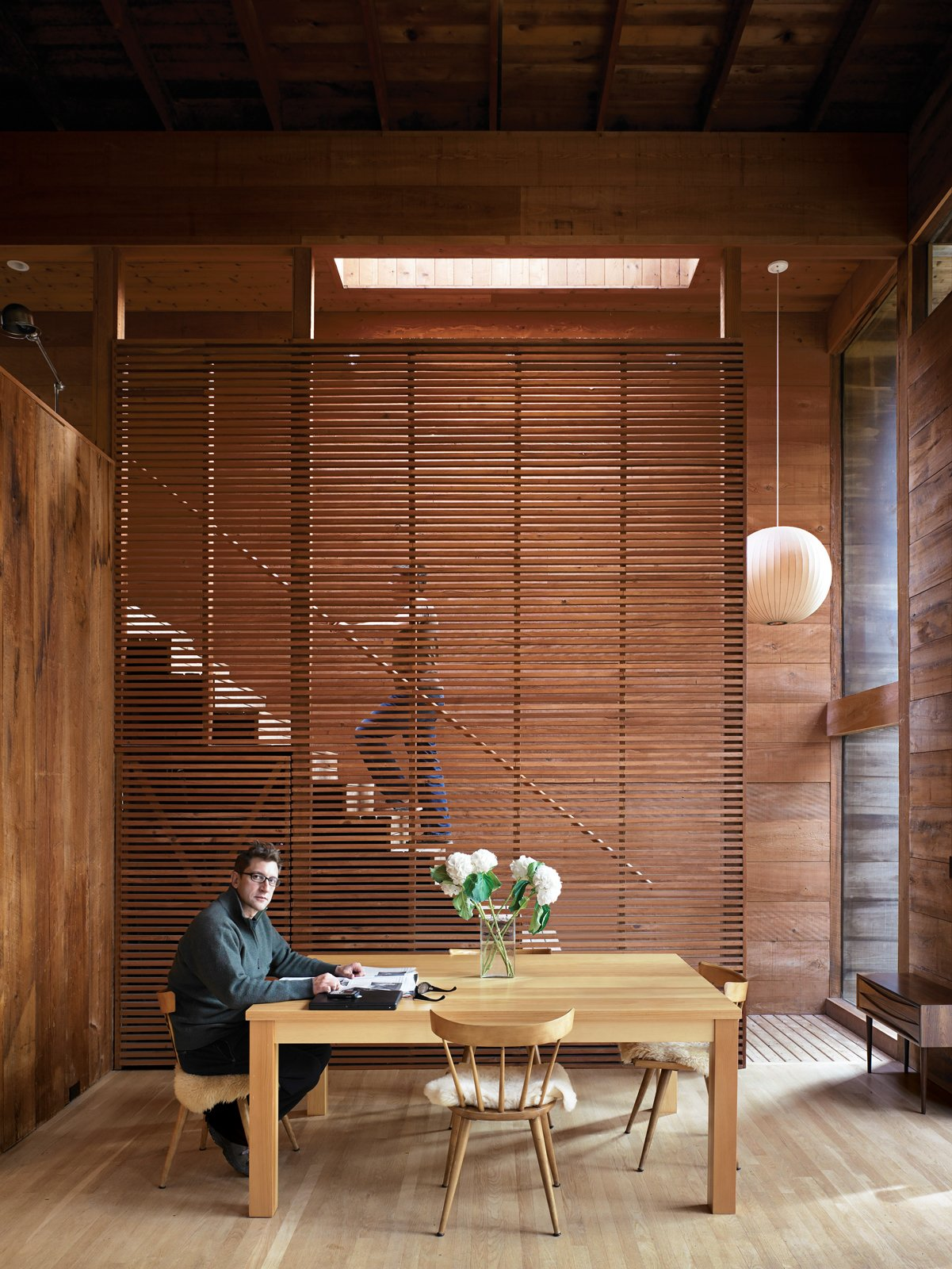 Dining Room, Table, Chair, and Light Hardwood Floor Dolce sits at the dining-room table in front of the elegantly slatted cypress divider, which separates the living space from the new staircase.  Best Photos from Long Island Summer Home Gets a Modern Addition