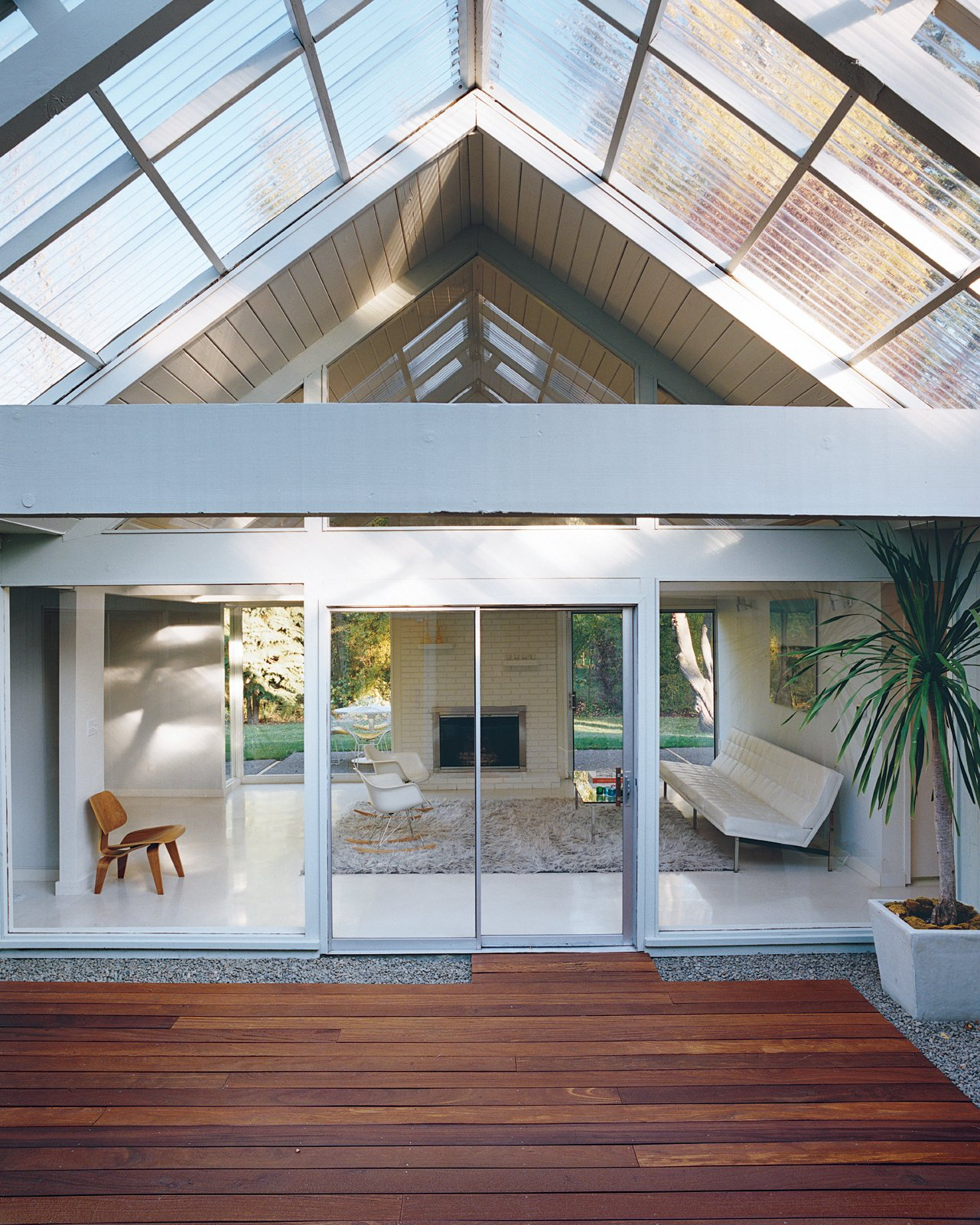 Outdoor, Large Patio, Porch, Deck, and Wood Patio, Porch, Deck The literal and figurative centerpiece of the house is the atrium, through which light filters into the rest of the house year-round.  Photo 10 of 15 in A Midcentury Modern Home in Southwest Portland