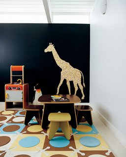 A deeply saturated blue hue colors the playroom wall.