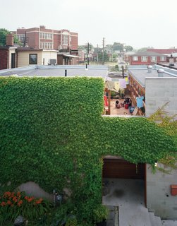A wide cut across the top of the structure made room for a second-floor courtyard where the family can catch some sun but maintain their privacy. On the ground level, the front door is tucked into an ivy-covered alcove lined with ipe, a material used throughout the house.
