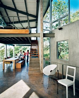 Exposed beams and a cantilevered loft soar over the high-traffic eating area, giving the family a sense of spaciousness.