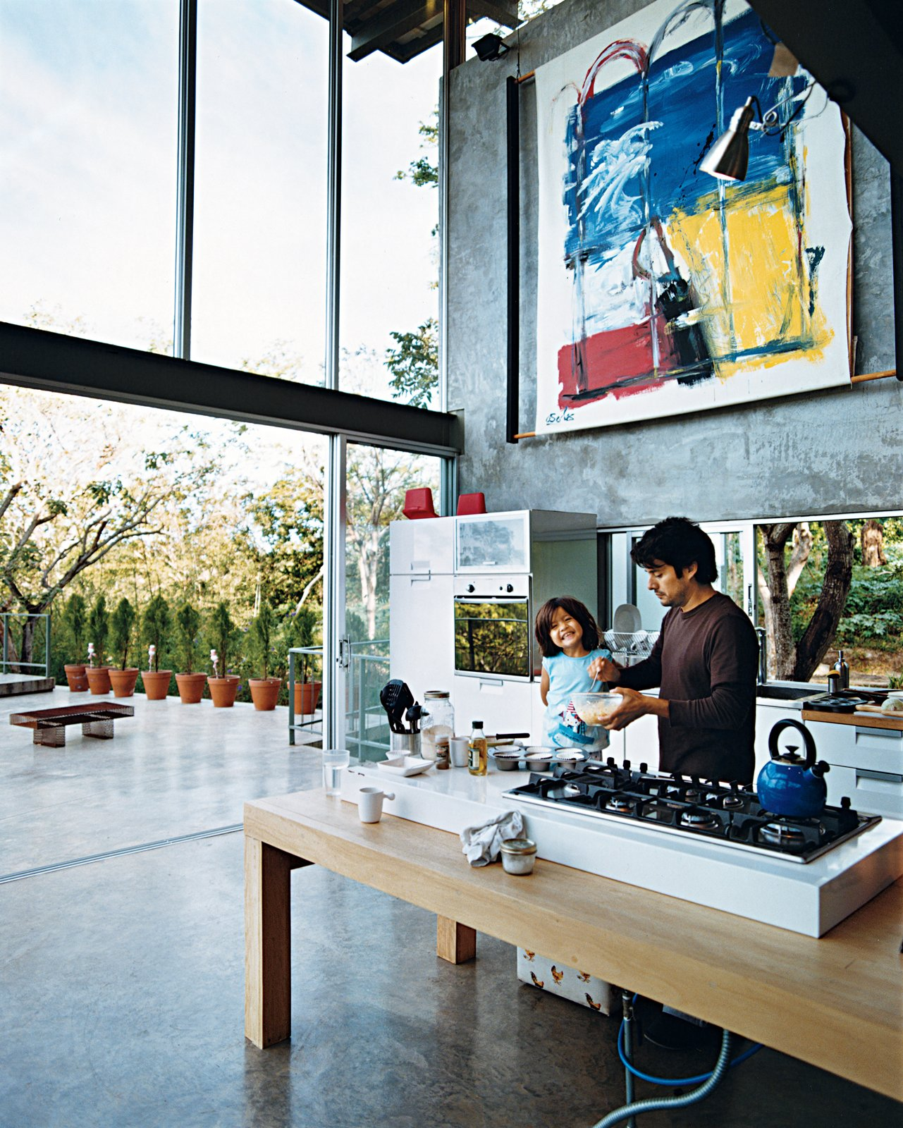 Kitchen, Wood Counter, Concrete Floor, and White Cabinet José Roberto, who says his family is always cooking something, prepares a snack with Jimena on the Ariston gas cooktop installed on the custom table.  Best Photos from Welcome to the Jungle
