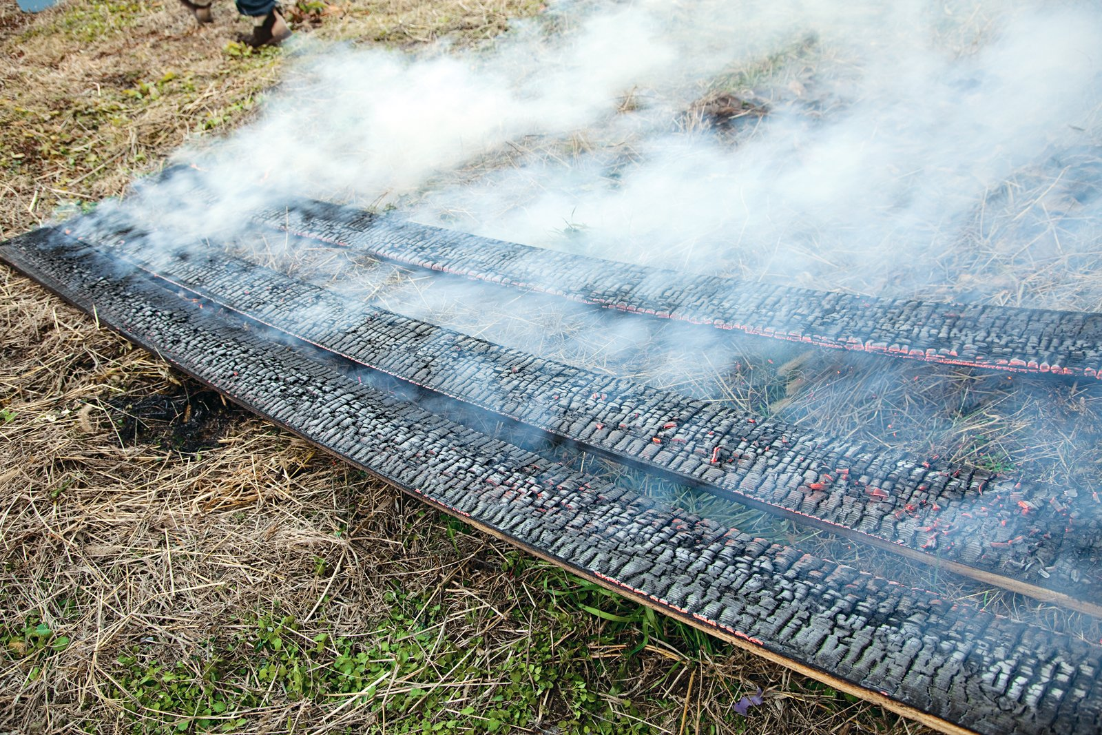 After the flames have been put out, the boards continue to crackle and smoke. Charring the boards properly requires a delicate balance between just enough burning, but not too much.  Photo 19 of 23 in Terunobu Fujimori