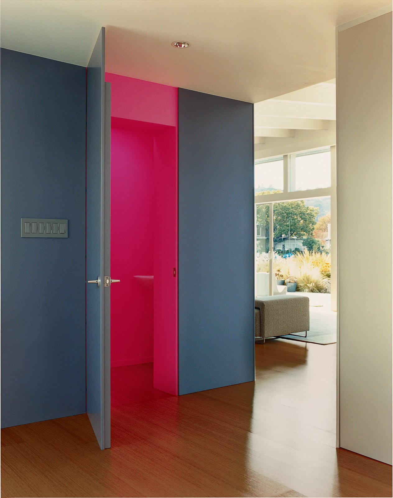In the foyer, Deam left one surprise: The neon-pink guest bathroom is hidden behind heavy, dark-gray walls.  Best Photos