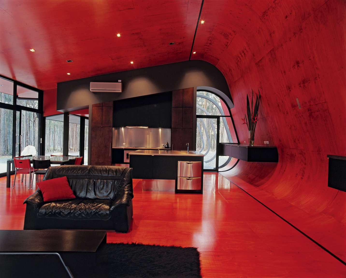 Living Room, Sofa, and Rug Floor The glowing interior palette of bright pinks and reds is sharpened by jet-black steel frames, water tanks, and roofs, while black window frames and joinery bring out the red glow of the internal plywood lining.  Photo 1 of 20 in 20 Modern Living Rooms from Black, Red, and Green All Over