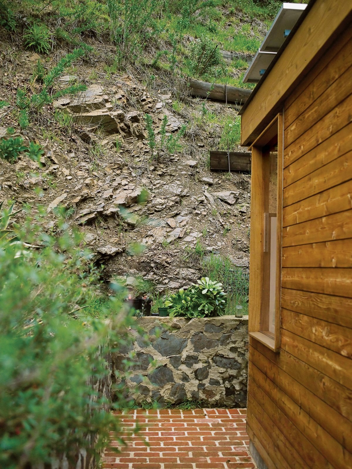 The steep canyon wall rises directly behind the house.  Photo 10 of 12 in Compound Addition