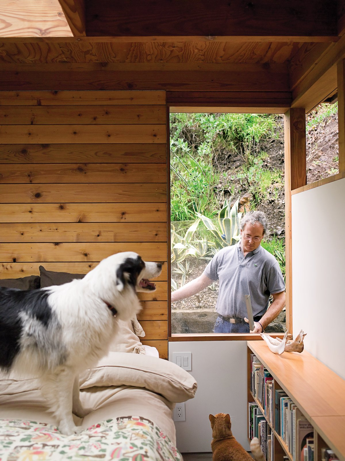 Bedroom, Bed, Shelves, Storage, and Bookcase In the master bedroom, a removable window provides egress, as required by code.  Photo 21 of 25 in Leap Into the Year of the Dog With These 25 Pups in the Modern World from Compound Addition