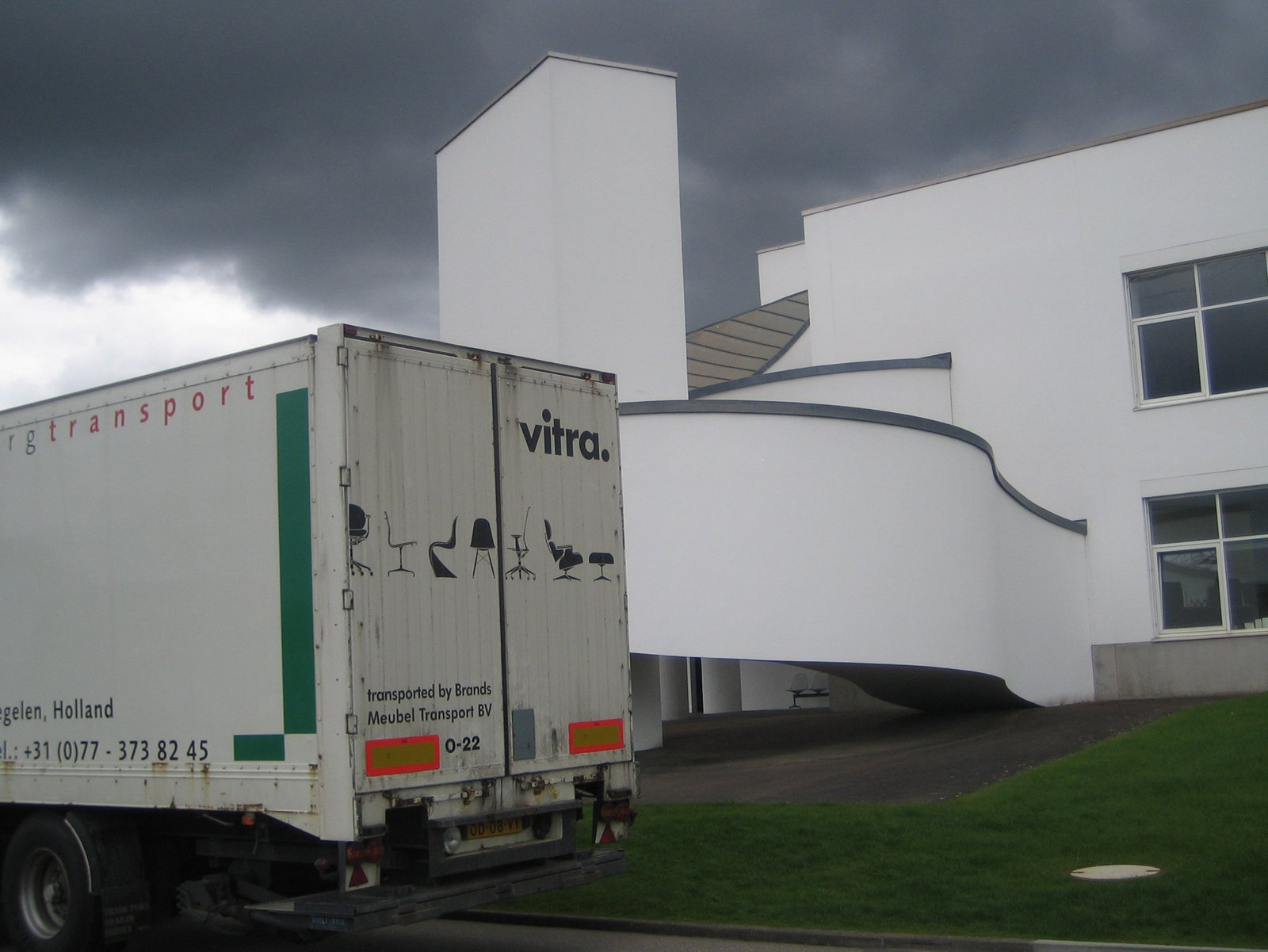 I loved this image of another of Gehry's buildings on campus playing backdrop to a Vitra delivery truck. The darkening sky gives the whole affair a rather ominous look.  Touring the Vitra Campus  by Aaron Britt