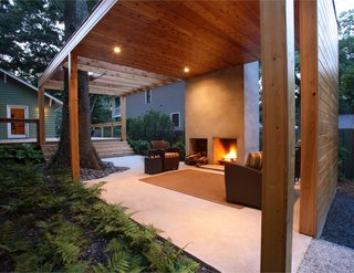 "The outdoor living room features a fireplace inspired by Frank Lloyd Wright's Usonian ""heart of the home"" hearth philosophy."