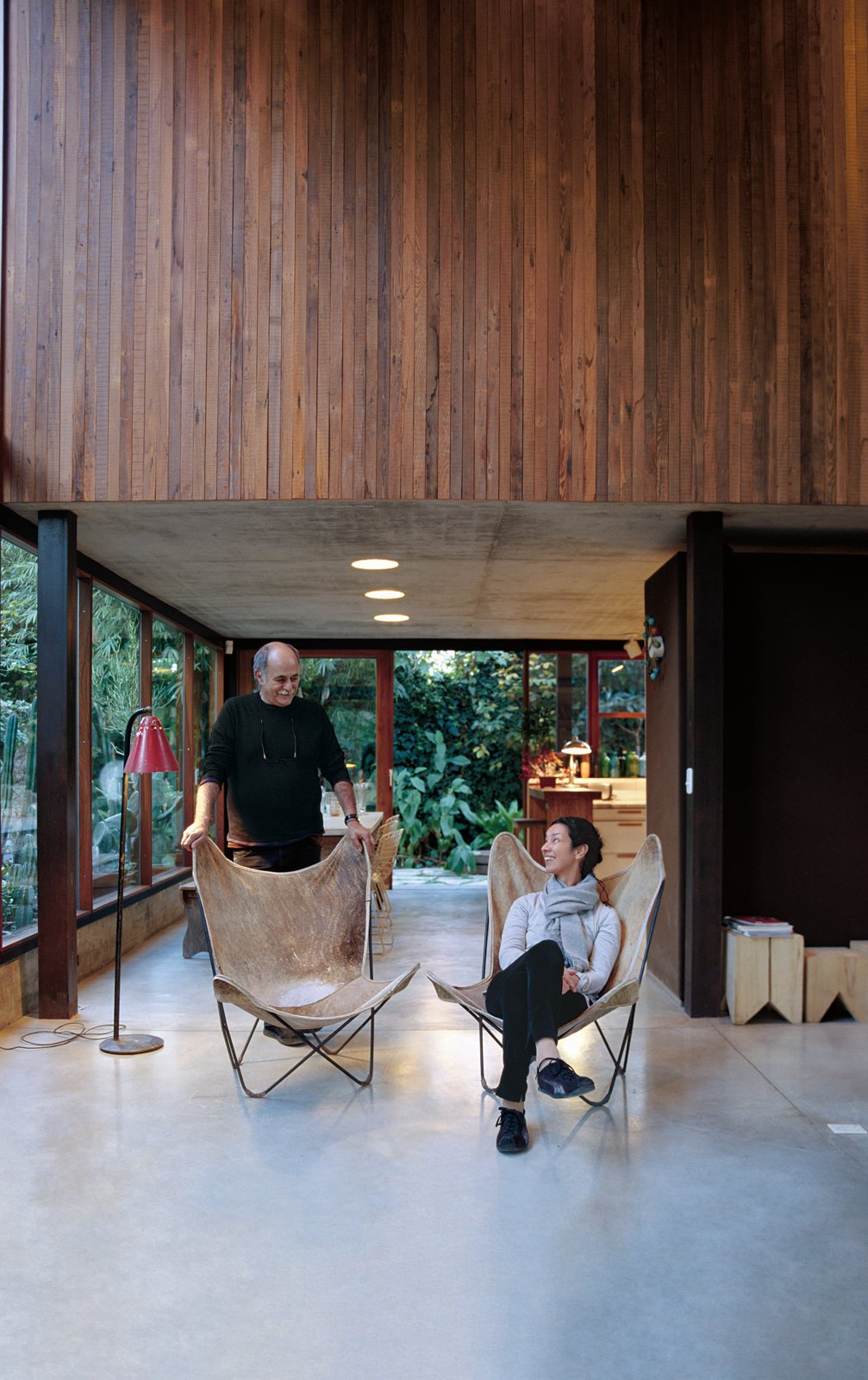 """Living Room, Chair, and Concrete Floor Sticotti and Hernaez relax in their living room, where custom-built windows and sliding doors enhance the indoor-outdoor effect.  Search """"where pigs fly"""" from Net Assets"""