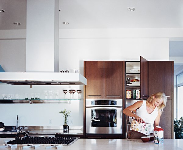 Jill prepares breakfast in the custom kitchen, which features a Roman travertine-topped work island.