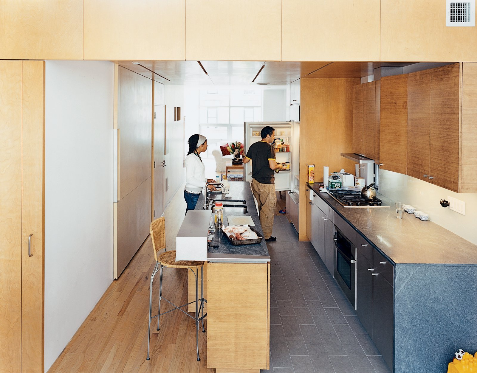 """Kitchen, Undermount Sink, Wood Cabinet, Stone Counter, Range, and Medium Hardwood Floor In the kitchen, the architects contrasted the oak floor, bamboo cabinetry, and birch walls and ceiling with what architect Jonathan Knowles calls """"a family of grays"""": granite floor tiles, limestone countertops, and the steel stairway. The birch wall behind Yvette is actually the sliding door to the pantry closet.  Take Me to Birch: 8 Houses that Make Use of Birch Wood by Luke Hopping from Harlem Renaissance"""