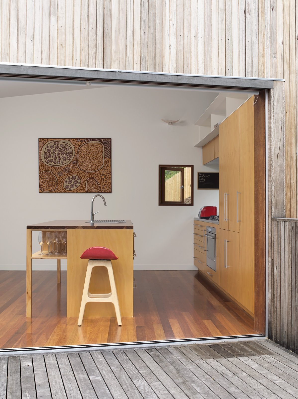 A painting by Aboriginal artist Yinarupa Gibson Nangala hangs in the kitchen, with a barstool from Danish designer Erik Buch in the foreground.  Photo 2 of 10 in Pedigree Charted