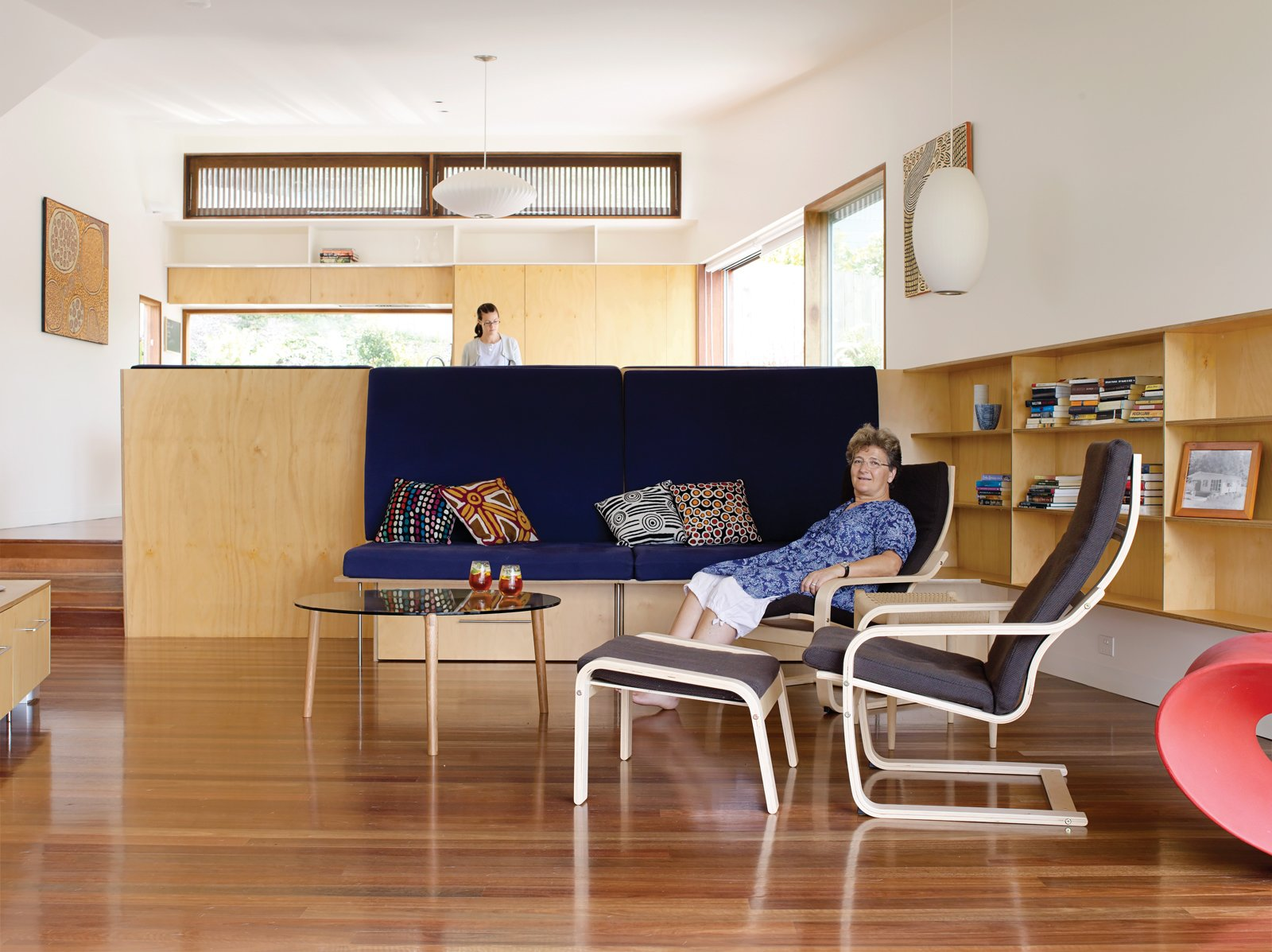 Hannah Ferguson relaxes in her living room. Her daughter Joanna prepares dinner in the open kitchen, behind and above the plywood banquette designed by the architects.  Photo 3 of 10 in Pedigree Charted