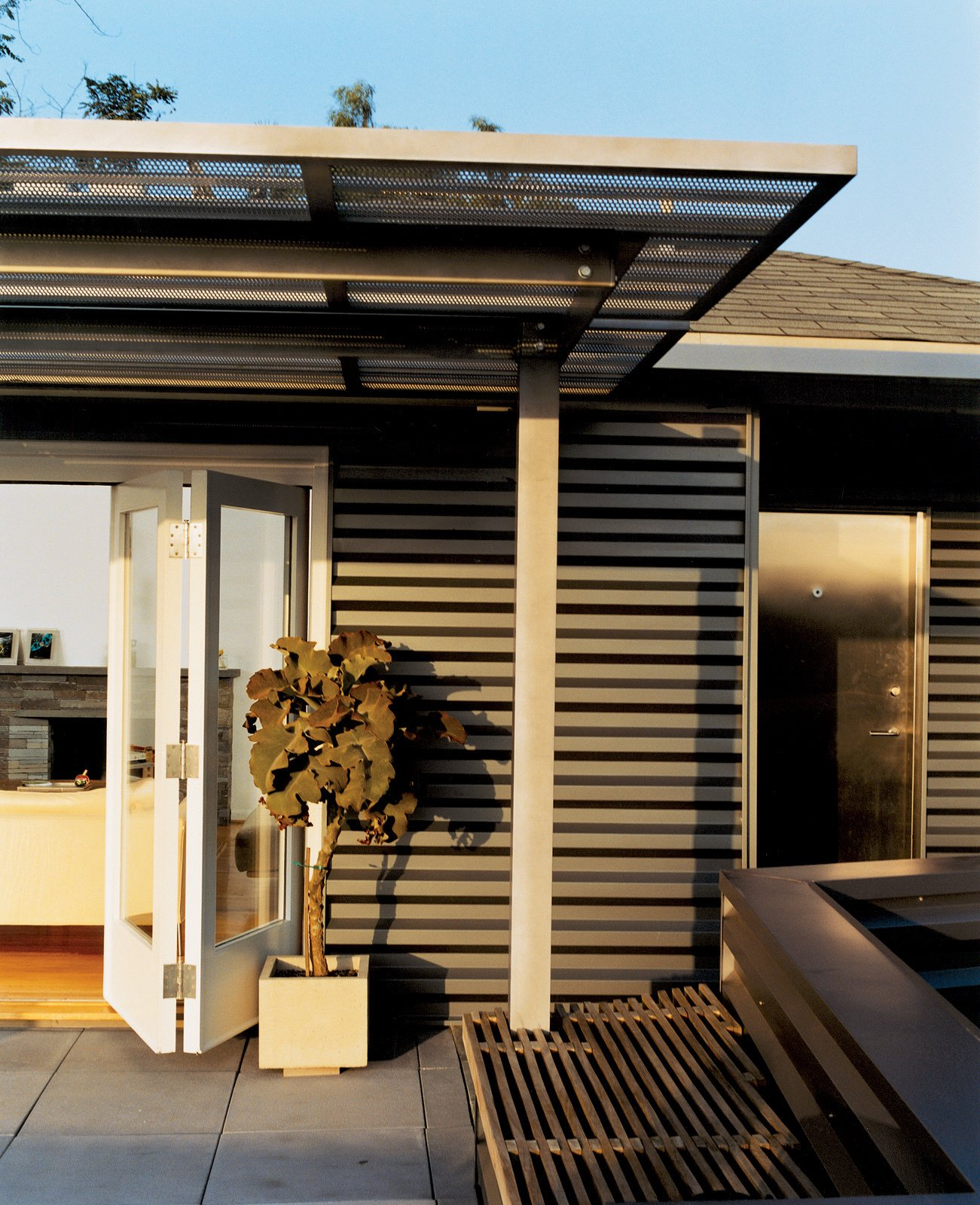 Day skinned the house in corrugated-aluminum siding, a tough industrial palette he picked up while designing airports. The corrugated stainless steel canopy was fabricated by Day's former SCI-Arc classmates.  Photo 3 of 12 in Way Out West