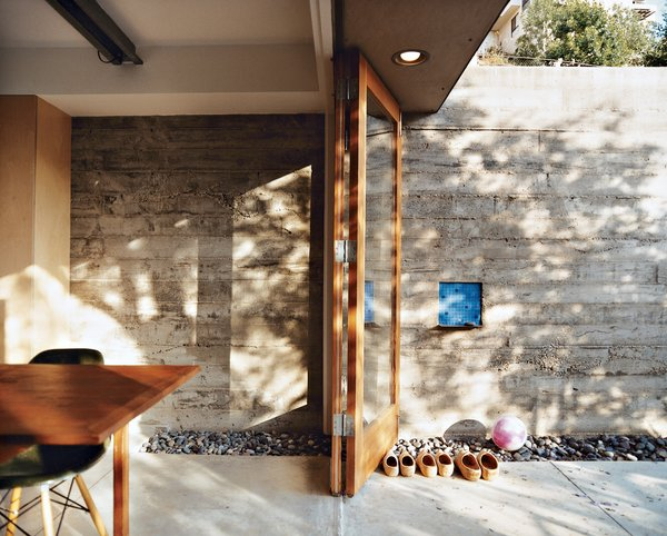 The elevated dining room opens out to a side patio, which climbs the wall just behind the house.