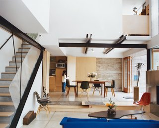 """The steel framing used for the house was left partially exposed. Other pragmatic touches with longevity and economy in mind are evident throughout, such as the screwed-down birch plywood stair treads that can simply be flipped over when worn out. Most seating below by Charles and Ray Eames. The coffee table by Paul Laszlo is, says Fung, """"probably the nicest thing we own."""""""