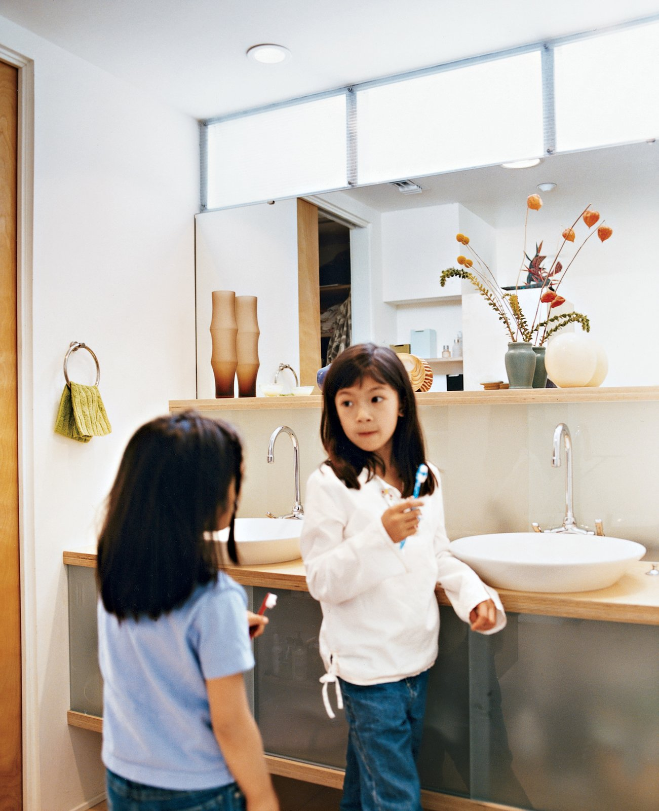 """Bath Room, Vessel Sink, Wood Counter, and Ceiling Lighting Kai and Téa brush their teeth in the upstairs bathroom shared by all. """"We went with the 1950s thing—a family bathroom,"""" explains Blatt. The sinks are by Kohler.  Photo 7 of 9 in How This Couple Broke The Rules in a LA Suburb"""