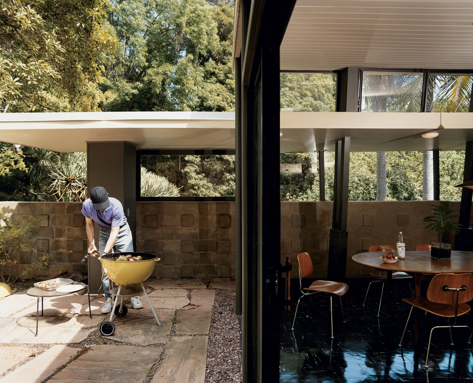 Outdoor, Large Patio, Porch, Deck, and Stone Patio, Porch, Deck In his writing geared toward builders, A. Quincy Jones encouraged using large panes of glass and sliding doors to bridge the exterior and interior. Here, Nick Roberts puts the philosophy to good use for a weekend barbecue.  Photo 2 of 7 in Mutual Fulfilment