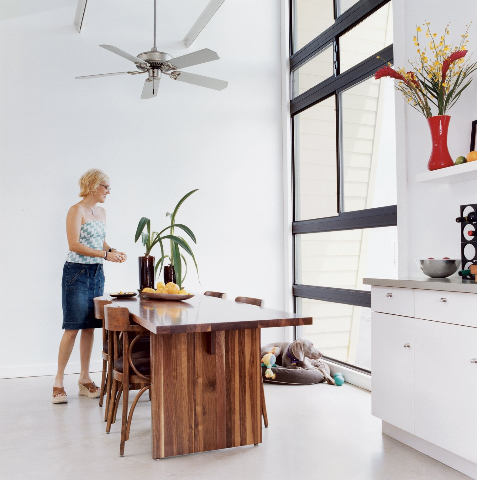 Custom furniture softens the house's aesthetics, including a dining table by AXIS Millwork and Fabrications. Ceiling fan by Craftmade.  Photo 3 of 10 in Big Easy Living