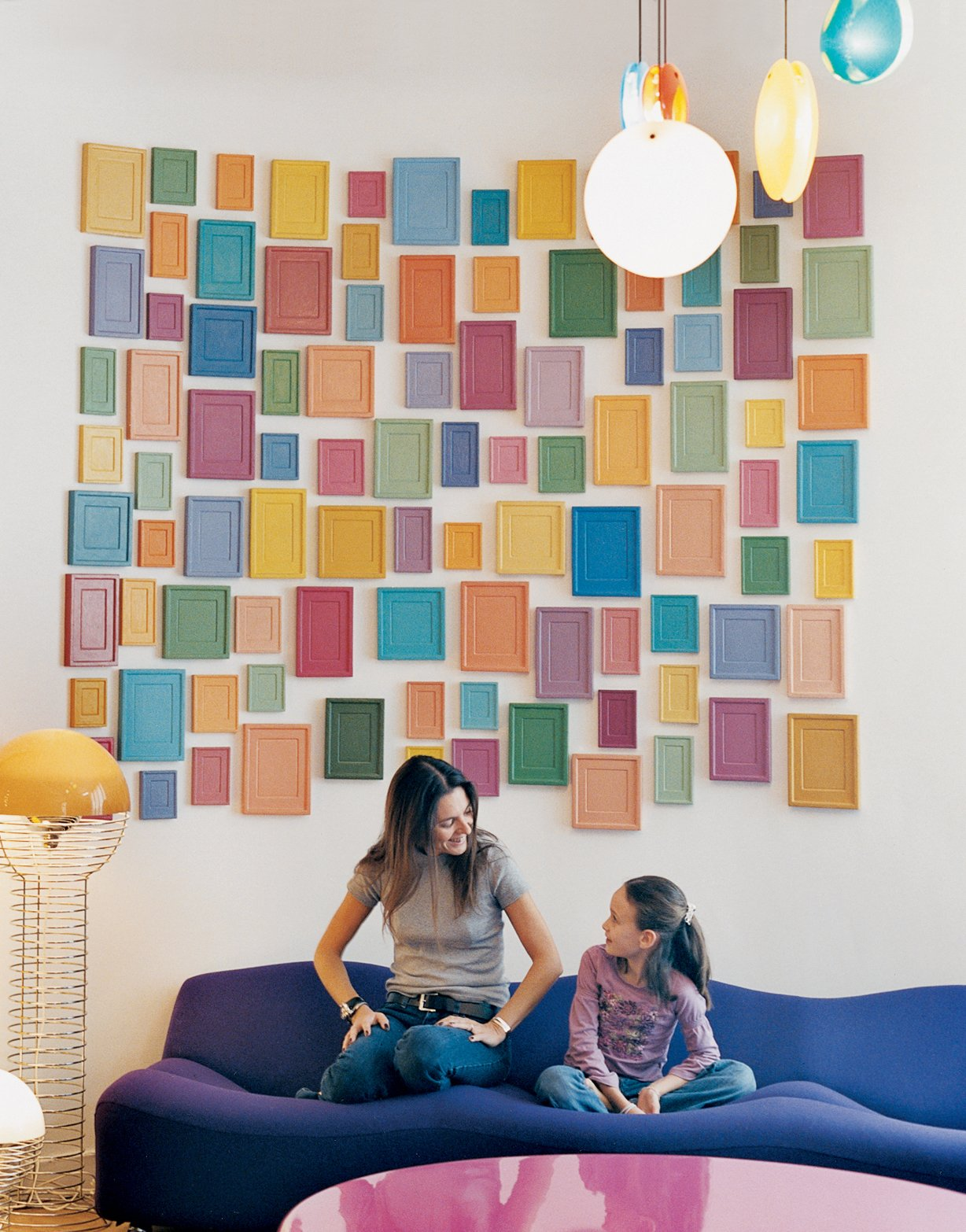 Living Room, Sofa, and Pendant Lighting Clémence and daughter Clara, nine, relax on a purple Pierre Paulin 261 sofa below an installation by artist Alan McCollum. A small family of Verner Panton 1969 Wire lamps, featured in the inaugural Kreo exhibition, live to the left.  Photo 6 of 15 in How to Design with Pink from Like a Kid in a Candy Store