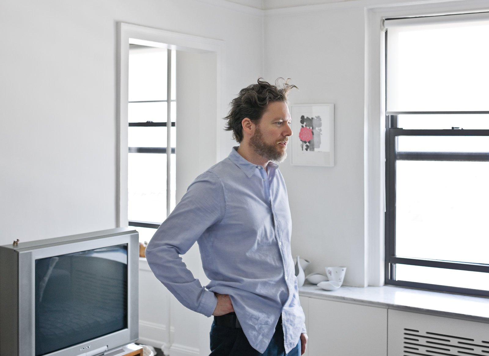 """Pulver and Mike worked together to devise a combination radiator cover and storage system that runs below the windows, from room to room, throughout the apartment. The screen has a slotted pattern, which Mike and Pulver painstakingly drafted—""""We looked at 30 different variations,"""" Pulver recalls—and Pulver CNC milled into wood panels.  Photo 10 of 13 in Creative Renovation in Brooklyn"""
