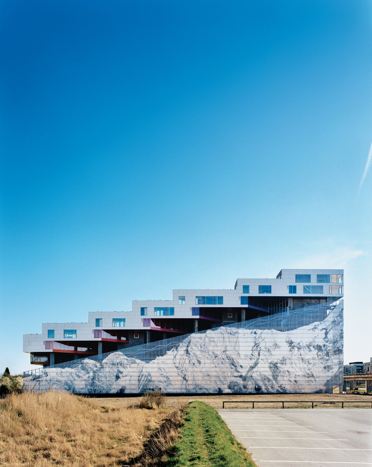 Completed in 2008, the Mountain Dwellings is the second of BIG's three projects in Ørestad, a new neighborhood in Copenhagen where development is attracting many new inhabitants. The result does looks like a mountain—hence the building's name and the inspiration for the mural of Mount Everest that adorns the 82-foot-high facade.  Photo 1 of 20 in Mountain Dwellings Urban Development in Copenhagen